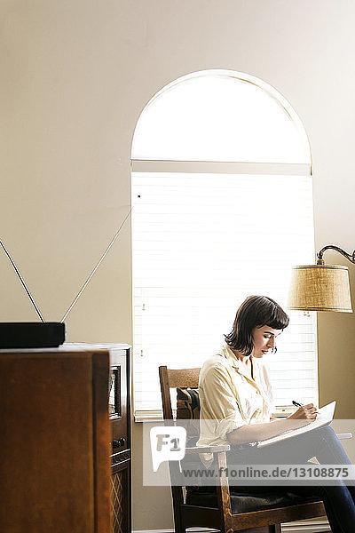 Seriöse Frau schreibt auf Buch  während sie zu Hause am Bogenfenster sitzt