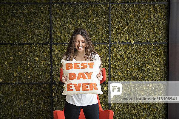 Glückliche junge Frau hält Kissen mit dem besten Text des Tages  während sie zu Hause an der Wand steht