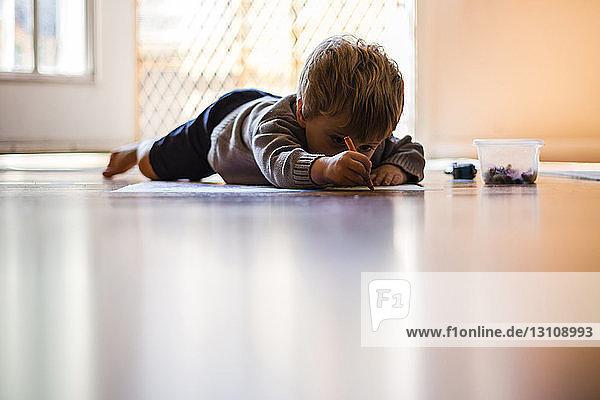 Oberflächenniveau eines Jungen  der im Liegen zu Hause auf Papier zeichnet
