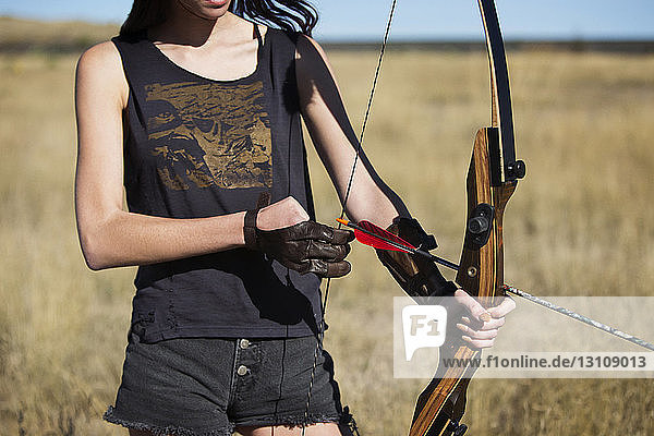 Midsection of woman with bow and arrow on field