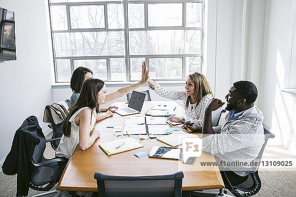 Happy businesswomen high fiving while sitting with colleagues in board room
