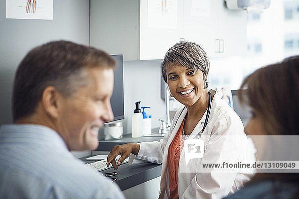 Glückliche Ärztin betrachtet Paar in der Klinik Glückliche Ärztin betrachtet Paar in der Klinik