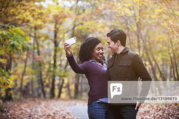 Glückliches Paar schaut sich an  während es im Wald Selbsthilfe betreibt