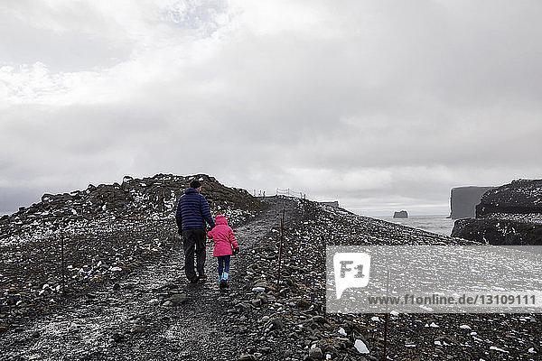 Rückansicht des Vaters und der Tochter beim Wandern auf dem Berg bei Dyrholaey Island vor bewölktem Himmel