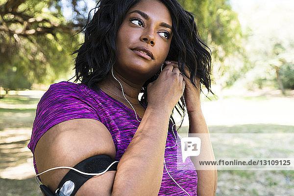 Frau trägt Kopfhörer beim Sport im Park