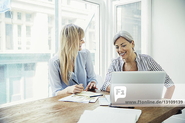 Happy businesswomen discussing over laptop in board room at creative office