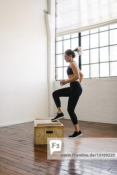 Seitenansicht einer Athletin  die auf einer Holzkiste in einer Turnhalle springt