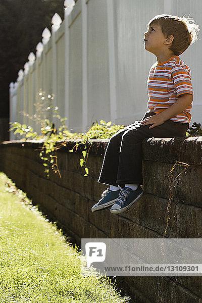 Nachdenklicher Junge sitzt auf Stützmauer gegen Zaun