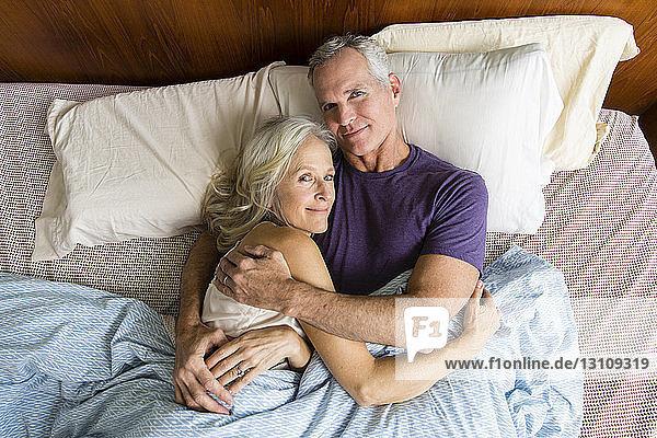Porträt eines selbstbewussten Paares  das zu Hause auf dem Bett liegt