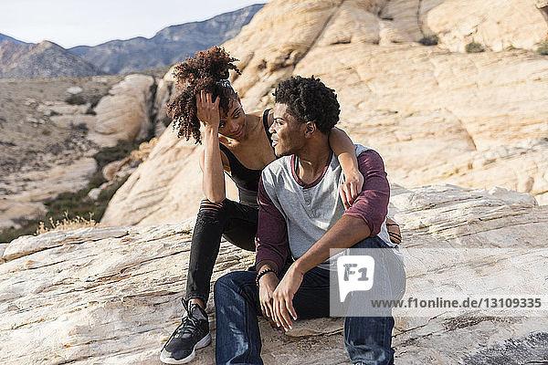 Paar sieht sich an  während es auf einer Felsformation sitzt