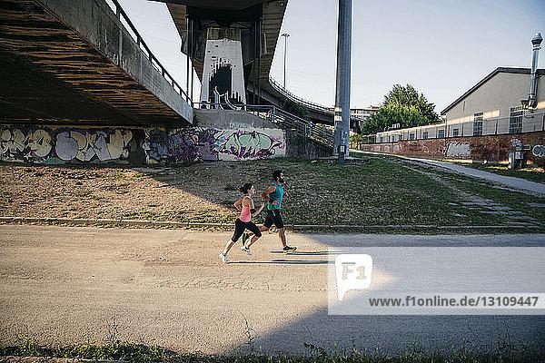 Hochwinkelaufnahme eines jungen Paares  das gemeinsam auf einem Fußweg joggt