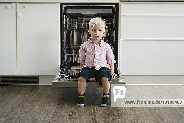Full length portrait of cute boy sitting on dishwasher door at home