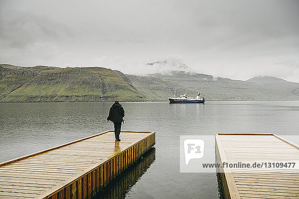 Rear view of man standing on pier over sea against mountains