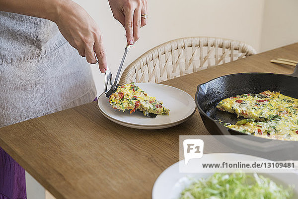 Cropped image of woman serving omelet in plate at table