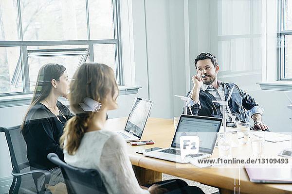 Geschäftsleute  die während einer Besprechung im Büro diskutieren  durch Fenster gesehen