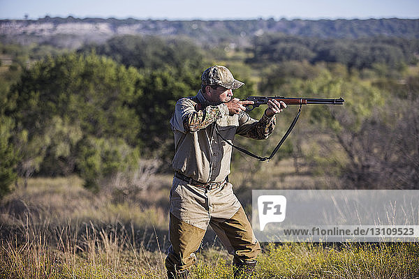 Hunter aiming with rifle while standing on grassy field