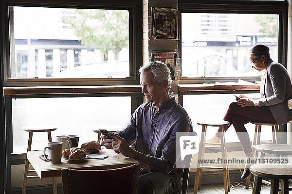 Kunden,  die telefonieren,  während sie im Cafe am Tisch am Fenster sitzen