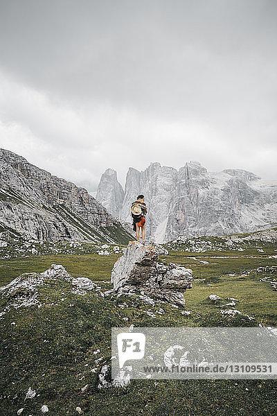 Rückansicht eines auf einem Felsen stehenden Wanderers vor bewölktem Himmel