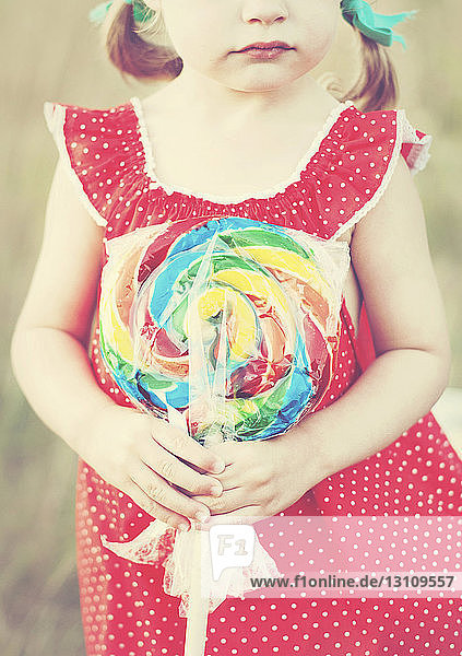 Midsection of girl holding multi colored candy outdoors