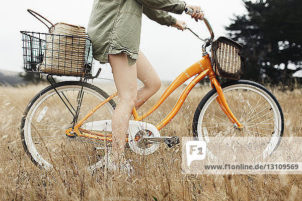Low section of teenage girl riding bicycle amidst plants on field
