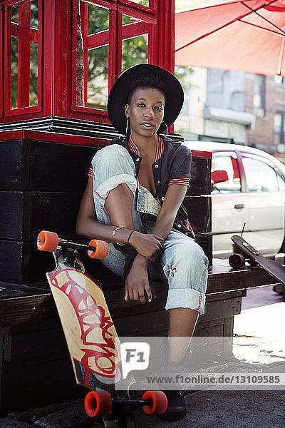 Porträt einer jungen Frau  die an Skateboards auf einer Stützmauer sitzt