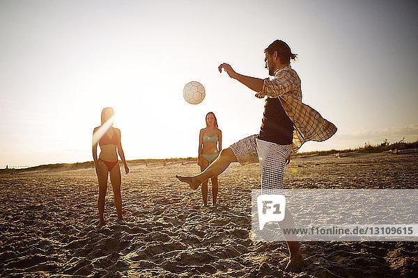 Freunde spielen Fussball am Strand gegen den Himmel