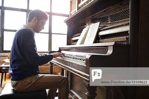 Side view of man playing piano by window at home