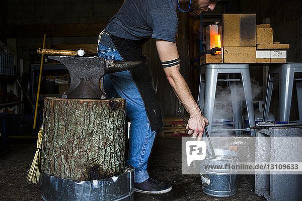 Schmied legt in Werkstatt Zange in Wassereimer Schmied legt in Werkstatt Zange in Wassereimer
