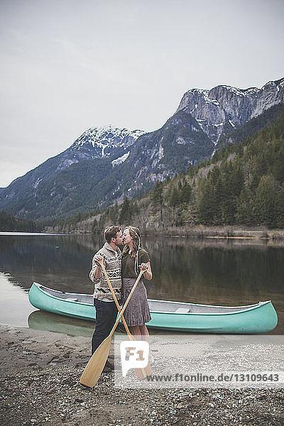Junges Paar hält Ruder  während es sich am Seeufer im Silver Lake Provincial Park küsst