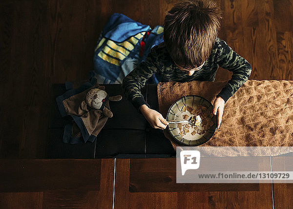 Overhead view of boy eating corn flakes at home