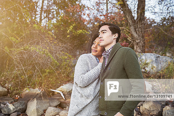 Couple looking away while standing in forest