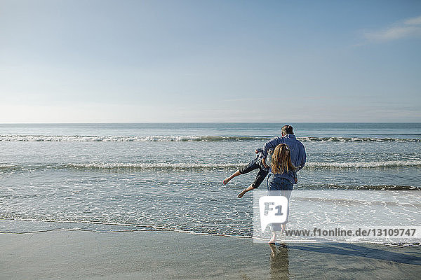 Playful father carrying daughter while walking towards sea at beach