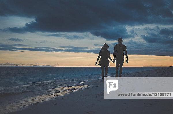 Scherenschnitt-Paar  das sich bei Sonnenuntergang an den Händen hält und am Strand vor bewölktem Himmel spazieren geht