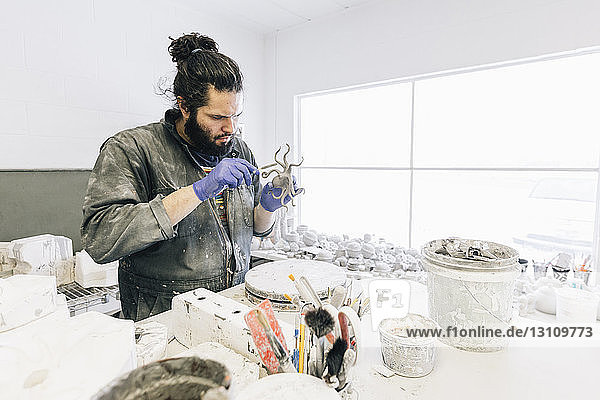 Focused craftsman making craft product at art studio