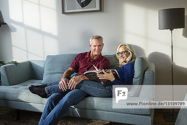 Smiling couple reading book while resting on sofa in living room at home