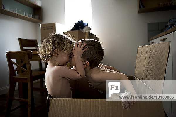 Brother kissing sister while sitting in cardboard box at home