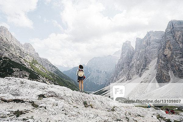 Rückansicht einer Wanderin  die auf einem Berg vor bewölktem Himmel steht