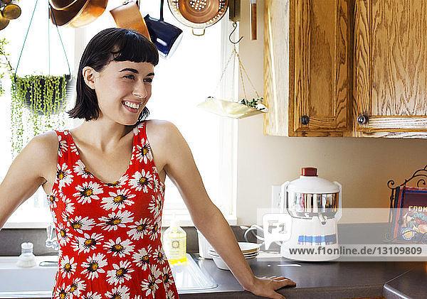 Lächelnde Frau steht zu Hause an der Küchentheke