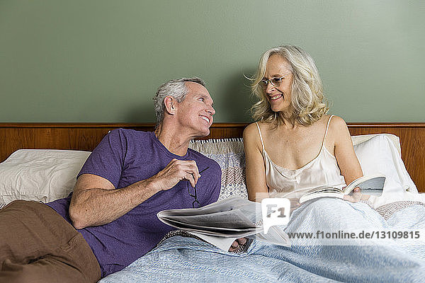 Smiling couple talking while resting on bed with book and newspaper at home