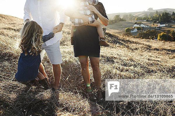 Niedriger Anteil der Familie auf dem Feld während eines sonnigen Tages