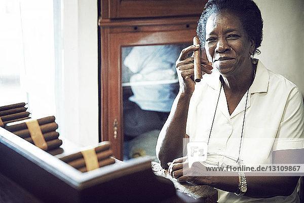 Porträt einer Frau  die in der Fabrik sitzend eine Zigarre hält