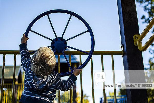 Rückansicht des Spinnrads eines Jungen auf dem Geländer eines Spielplatzes