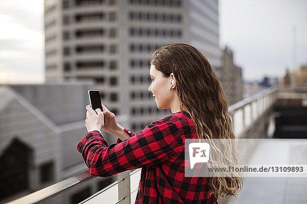 Seitenansicht einer jungen Frau  die ein Smartphone benutzt  während sie am Geländer auf der Terrasse steht