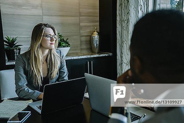 Seriöse Geschäftsfrau sitzt während der Sitzung mit Kollegen zusammen