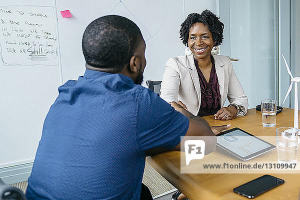 Geschäftsfrau gibt sich mit männlichem Kollegen die Hand