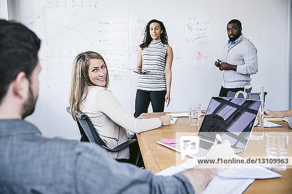 Kollegen schauen Geschäftsmann bei Besprechung im Sitzungssaal an