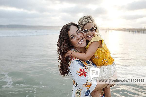 Porträt einer fröhlichen Mutter und Tochter am Strand