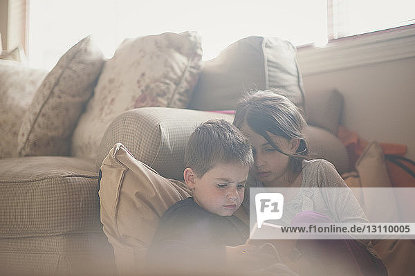 Girl looking at brother using tablet computer by sofa at home