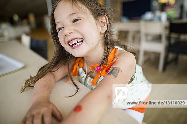 Close-up of happy girl looking away while sitting by wooden table at home