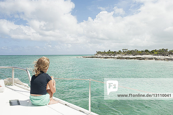 Rear view of girl sitting on boat while traveling in sea against cloudy sky